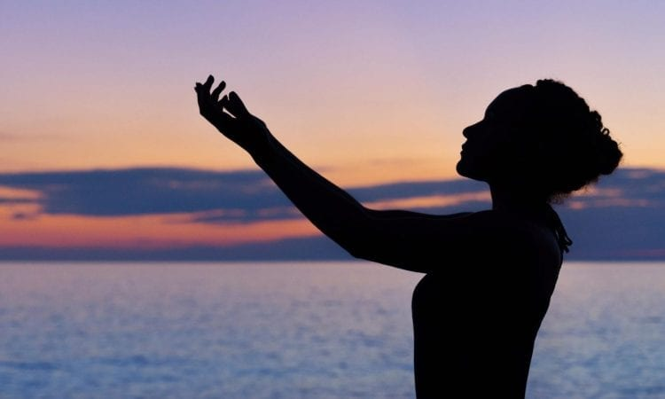silhouette of woman against the water with her hands reaching up